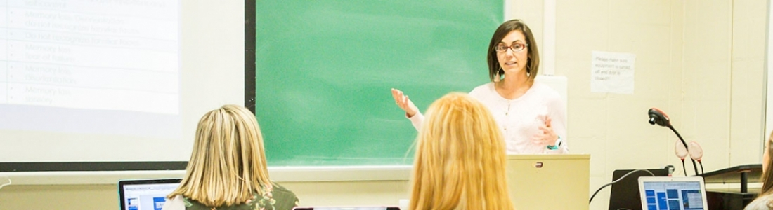 Instructor indicates to lesson on chalkboard in front of class